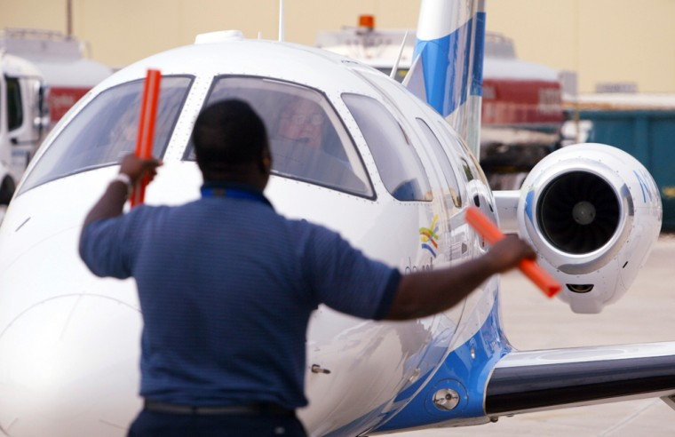 An airport worker directs an Eclipse 500 DayJet plane as it prepares to take off. A pair of 'air taxi' companies launching jet service this month from smaller airports will have an easier time attracting customers thanks to record delays plaguing major carriers. But experts say the service has the potential to worsen the congestion this new business model aims to avoid.