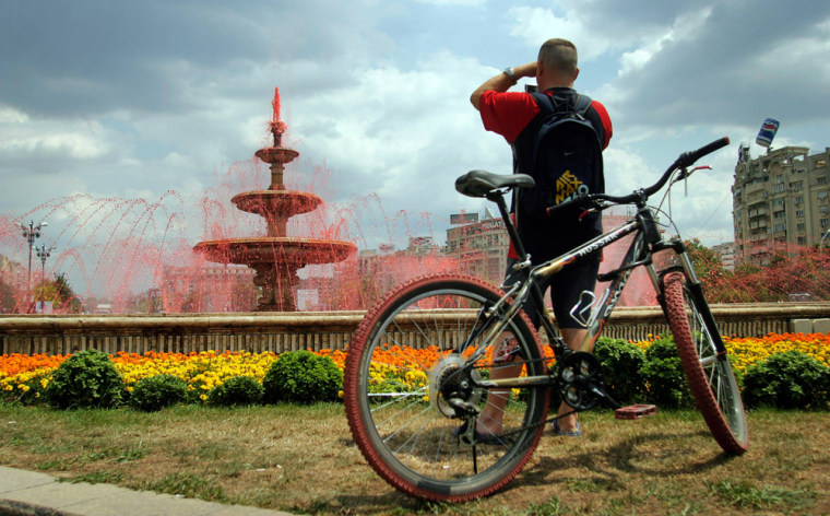 A man takes pictures of coloured water springing from public fountains in Bucharest