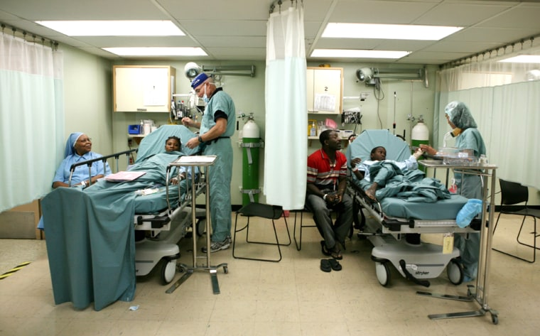 Doctors attend Haitian patients before they undergo surgery aboard the U.S. Navy hospital ship USNS Comfort Thursday offPort-au-Prince, Haiti. Hundreds of medical volunteers aboard the floating hospital are providing free services, includingvaccinations, eye exams, dental treatment and surgical procedures, for local residentsduring the ship'sregional goodwill mission.