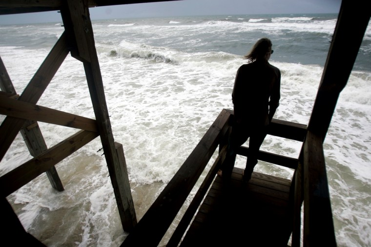 Yogi Harper watches from the deck of an ocean-front house at high-tide as Tropical Storm Gabrielle lurks offshore in Nags Head, N.C., on Sunday.