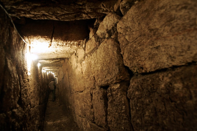 An Israeli archaeologist on Sunday walks along a drainage channel in the City of David next to Jerusalem's Old City. Scientists stumbled upon thetunnel two weeks ago during a survey, and say it figured in the Jewish escape from the city inthe year70.