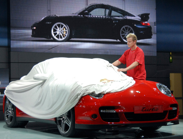 A worker covers a Porsche at in Frankfurt, Germany,on the eve of the International Auto Show.