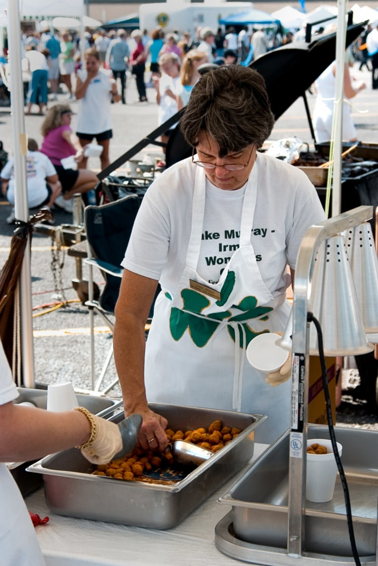 Jane Hiller, of the Lake Murray-Irmo Women's Club scoops fried okra into a cup at the Okra Strut in Irmo, S.C. The festival, which started in 1973, draws about 50,000 people to Irmo to celebrate the unusual green pod vegetable.