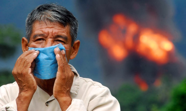A man wears a face mask to protect himself from the fumes near the site of an explosion at a gas pipeline belonging to state oil monopoly Pemex near Olmeaca