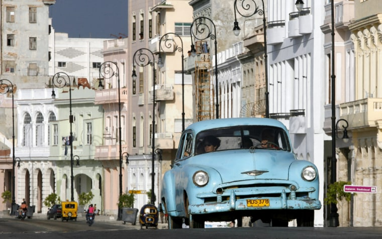 """Cubans ride in an old car on Havana's coastal """"Malecon"""". Traveling to Cuba is not illegal for Americans, but the Trading with the Enemy Act prohibits spending money on the island. If caught, unauthorized U.S. tourists can face civil fines of up to $55,000. Even Michael Moore is now being investigated for filming """"Sicko"""" without permission in Cuba."""