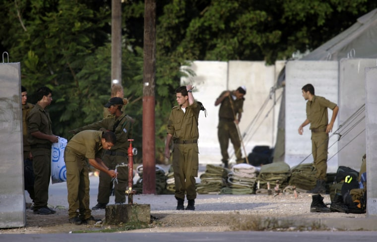 Israeli soldiers are seen at the site where a rocket, fired from the Gaza Strip, hit an army training base near the coastal city of Ashkelon, on Tuesday.