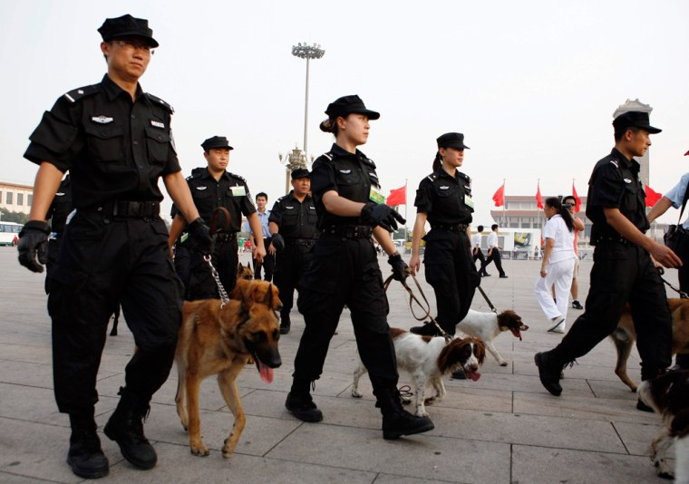 Police conduct security checks with dogs as they prepare for the one-year countdown celebrations for the 29th Olympic Games in Tiananmen Square in Beijing