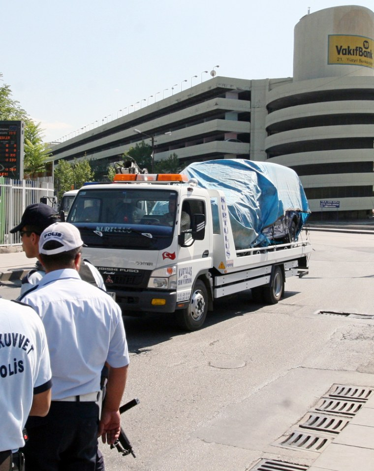 A security truck carries a bomb-laden vehicle hours after sniffer dogs discovered it parked in a multistory parking lot, in Ankara, Turkey, on Tuesday.