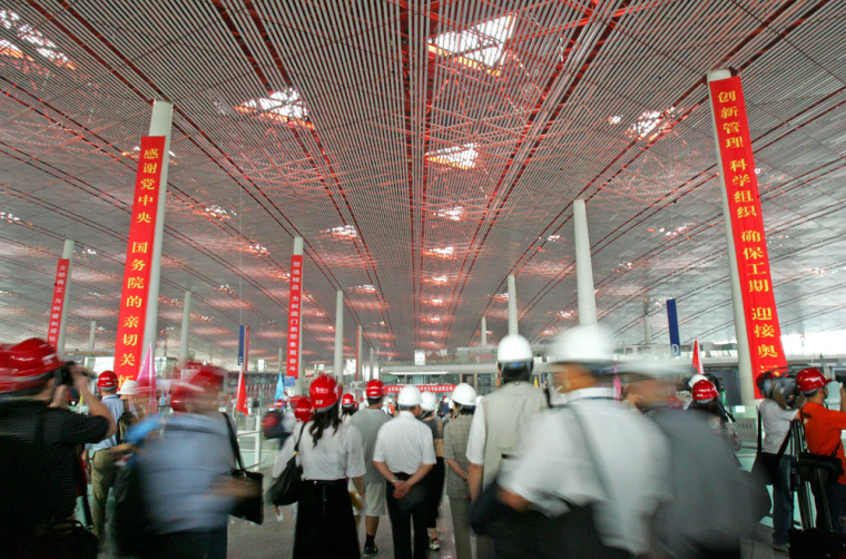 Members of the press wearing safety helmets enter Beijing's new Terminal 3 on Wednesday.