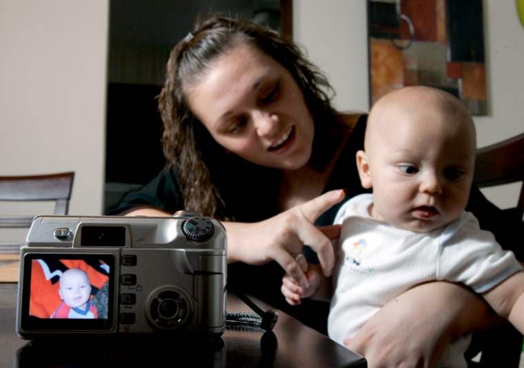 Amy Short poses for a photo with her 5-month-old son Jordan as he is seen on the back of his mother's camera Wednesday at their home in East Alton, Ill. Thanks to cheap and easy-to-use recording devices — digital cameras, camcorders, camera phones — today's kids are becoming the most documented generation ever, as parents, relatives and friends capture forever the first, second and hundredth smile.