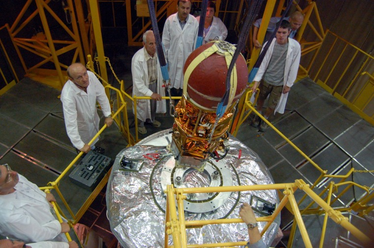 The YES2 experiment, which looks like a big red ball with an apparatus attached to the bottom, is lowered onto the larger Foton-M3 science satellite during preparations for launch from Russia's Baikonur Cosmodrome in Kazakhstan.