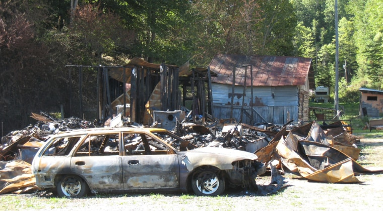 Timothy and Melissa Chandler's house and car, shown Wednesday,were destroyed after two men allegedly set the house on fire. Authorities called the case an example of vigilante justice.
