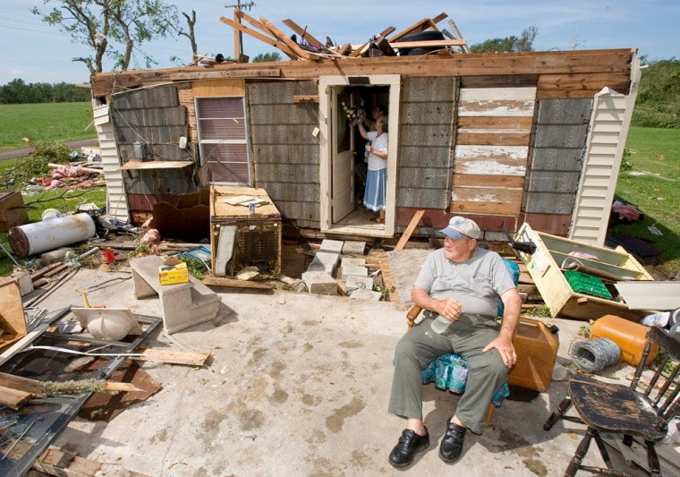 Jack Payton, 72, sits Thursdayin front of his High Island, Texas, home that was severely damaged by Hurricane Humberto'shigh winds.His wife, Connie, removes a wreath from their front door.
