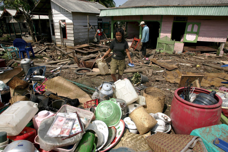 Residents collect their belongings from their damaged houses after a small tsunami