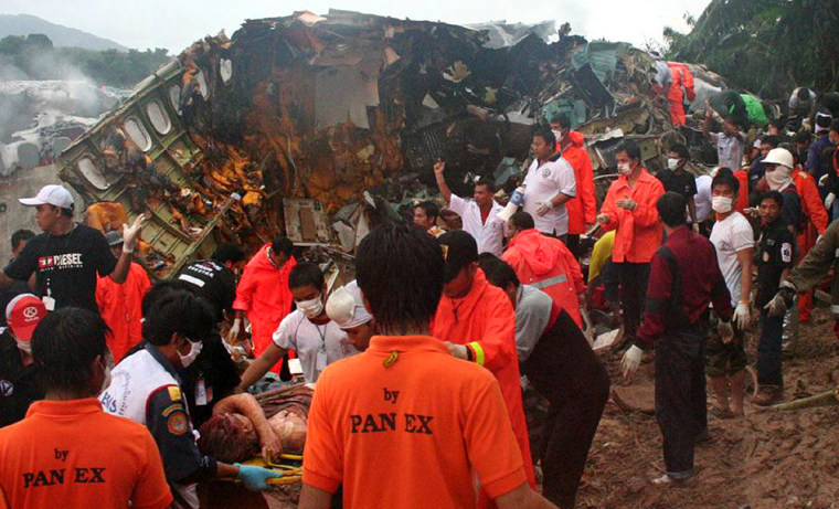 Rescue workers evacuate the injured from the  site of a plane crash at Phuket airport