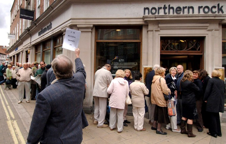 Customers line up outside a branch of the British mortgage lender Northern Rock in York England, as savers across the country seek to remove their money from the crisis-hit bank. Oneinvestor walks to the back of the queue to make a deposit. Treasury Secretary Alistair Darling sought to assure the bank's depositors that their money was safe, though former U.S. Federal Reserve Board chairman Alan Greenspan warned of difficulties ahead in Britain's booming housing market.