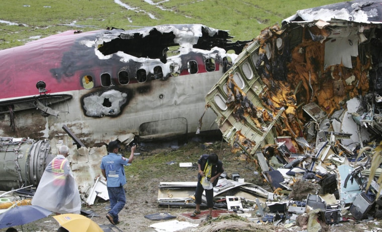 Thai rescue workers examine the scene of the One-Two-Go Airlines plane crash in Phuket, Thailand, Sept. 17. The passenger plane that crashed on Thailand's resort island of Phuket Sunday killed at least 90 people, mostly foreigners, an airline official said Monday.