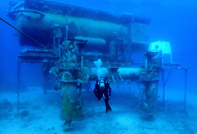 A diver swims by the Aquarius Reef Base, a permanent working undersea laboratory located off Key Largo, Fla., in the Florida Keys National Marine Sanctuary.