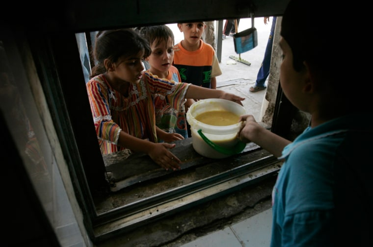 Poor residents receive food during the fasting month of Ramadan at the Sunni mosque of Abdul Qadir al-Gailani in Baghdad