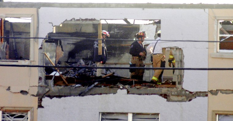 Florida firefightersexamine a three-story apartment building, which was home toup to 150 residents,that caughtfire after an explosionThursday.