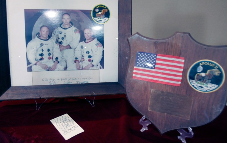 Shown are Apollo 11 items including a handwritten card, bottom left, containing a Bible verse that astronaut Buzz Aldrin planned to broadcast back to Earth. The notes fetched $180,000 at an auction of space memorabilia.