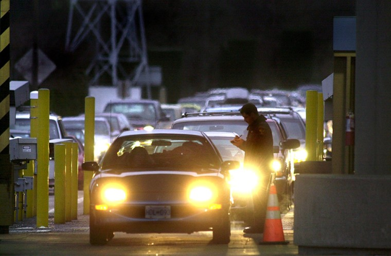 A US Customs officer (R) is on duty as cars line u