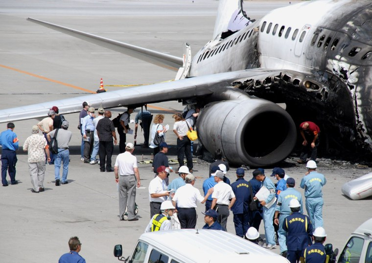 Japanese and U.S. investigators including Boeing officials, inspect the burned-out engine of Taiwan's China Airlines 737-800 jet liner that exploded after landing at the Naha airport in Japan's southern island of Okinawa, on Aug. 23. On Thursday, airport workers in Japan found a 28-inch fracture in the fuselage of a similar China Airlines Boeing 737-800.