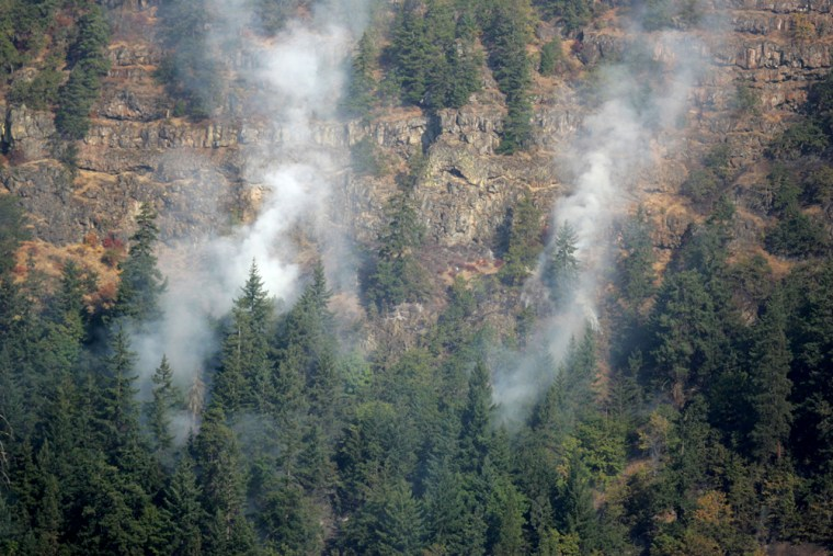 A wildfire burns along the cliffs overlooking the Columbia River near White Salmon, Wash., on Friday.