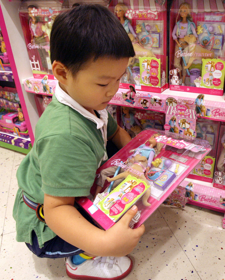 """A Chinese boy holding a Mattel """"Barbie and Tanner"""" still for sale in China despite being recalled in the U.S., at a department store in Shanghai last month. Mattel issued an extraordinary apology to China Friday, saying it was to blame for design flaws."""