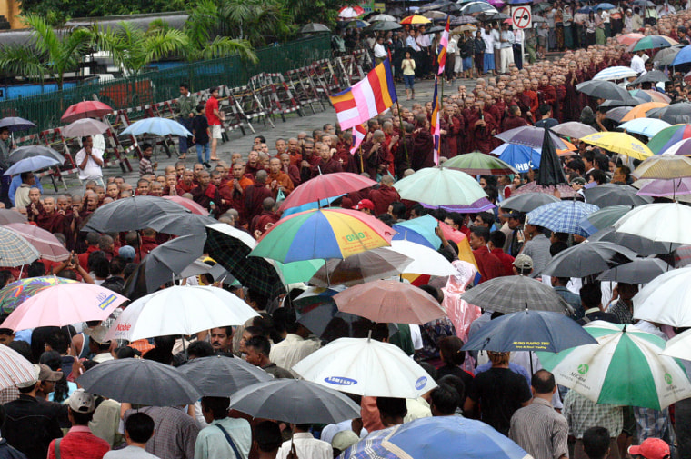 Buddhist monks gather in front of the city hall in Myanmar's largest city Yangon on Fridayafter marching from the famous Swedagon Pagoda. About 3,000 people including 1,500 Buddhist monks marched through the flooded streets.