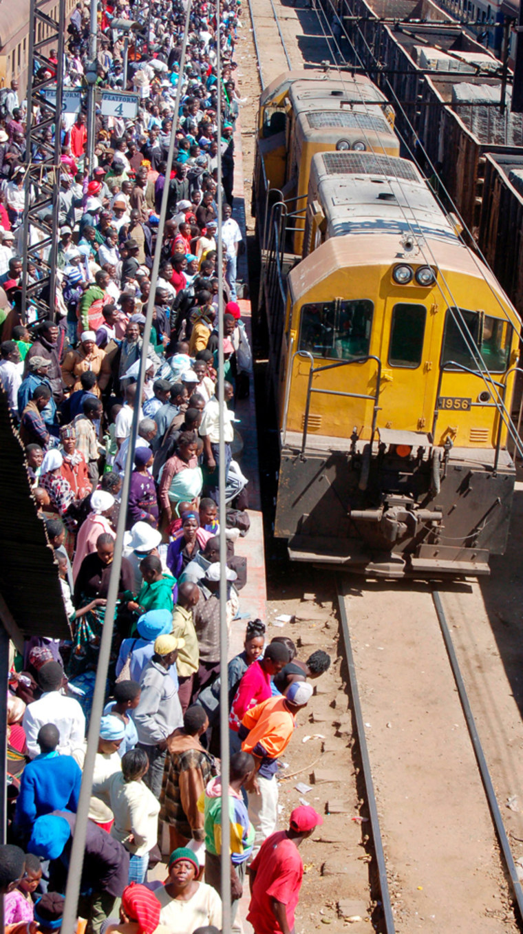 Zimbabweans wait for a domestic train in Harare, Zimbabwe, as the newly-appointed finance mnister massively devalues the local dollar in a bid to attract scarce foreign currency