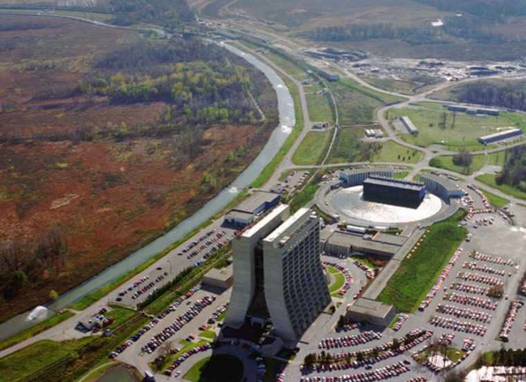 An aerial photo of Fermilab shows the futuristicWilson Hall alongside the cooling canal for theTevatron, with a prairie habitat inside the collider ring.