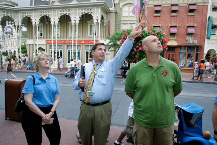 Rob Morton points out some things of note at Walt Disney World to two Miami Airport employees during a semiar on customer service.