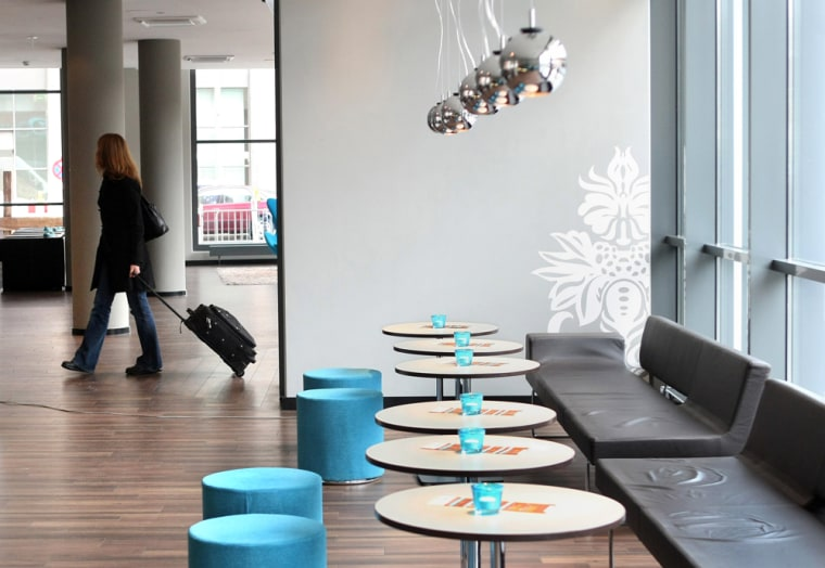 """A customer enters the lobby of Motel One in Berlin. Berlin's Mayor Klaus Wowereit once famously described his eternally broke city as """"poor, but sexy"""" — anda new crop of sleek budget hotels are betting that economy minded tourists and business travelers like it that way."""