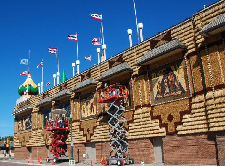 Workers on scissor lifts create murals out of corn on the side of the Corn Palace in Mitchell, S.D.Since the Corn Palace debuted in 1892, its palette has grown to 12 distinct shades of corn.