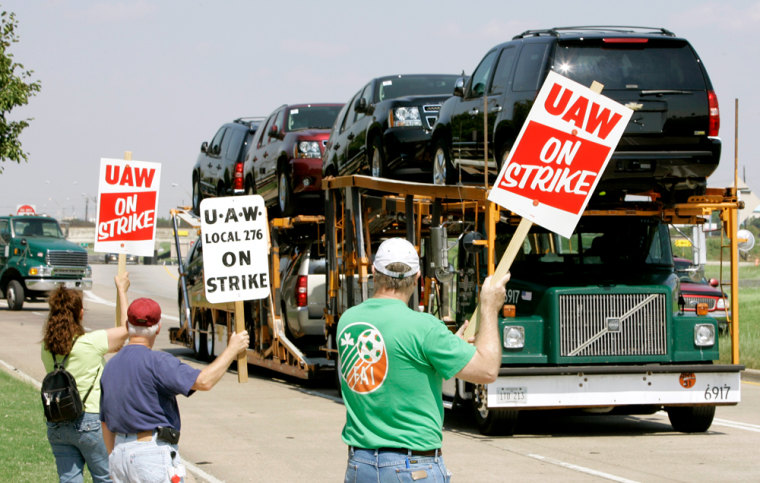 GM workers display strike signs at a plant in Arlington, Texas, Monday. Analysts expect the automaker to be able to ride out the first strike in the U.S. automotive industry since 1970, so long as it is a short one.