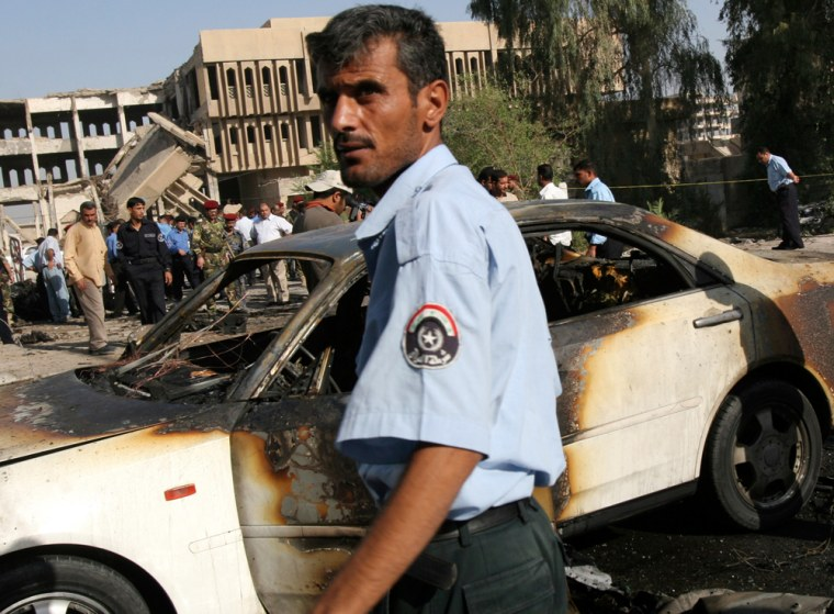 Police officers and onlookers gather at the scene of a car bombing Tuesday in the southern Iraqi city of Basra.