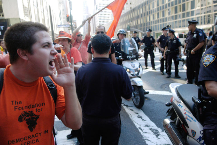 A protester yells at a passing police officer on Tuesday at a rally near the U.N. Demonstrators called for the impeachment and arrestof President Bush.