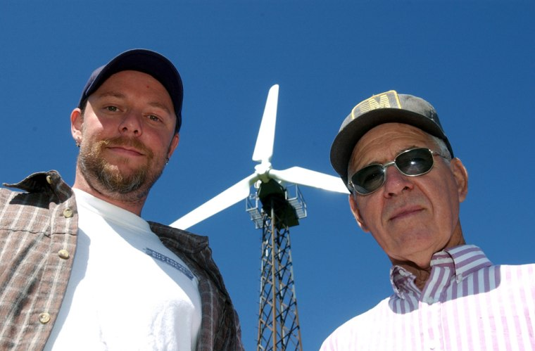 Brain Zachary and his father-in-law, Joseph Weishaar, stand in front of the electric wind turbine they erected on their farm just outside of Creston, Iowa.