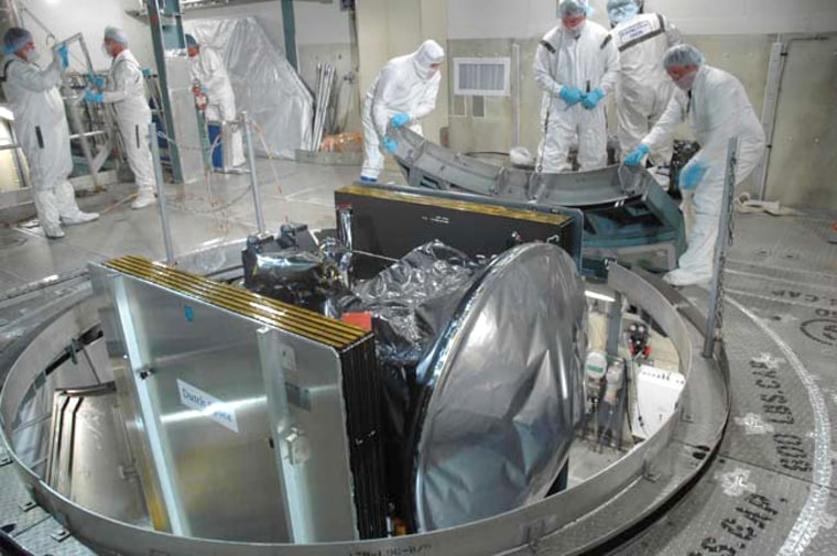 Launch pad workers prepare the Dawn spacecraft for its attachment to a Delta 2 rocket. A possibility of rain showers on launch day could delay Dawn's liftoff, NASA mission managers said.