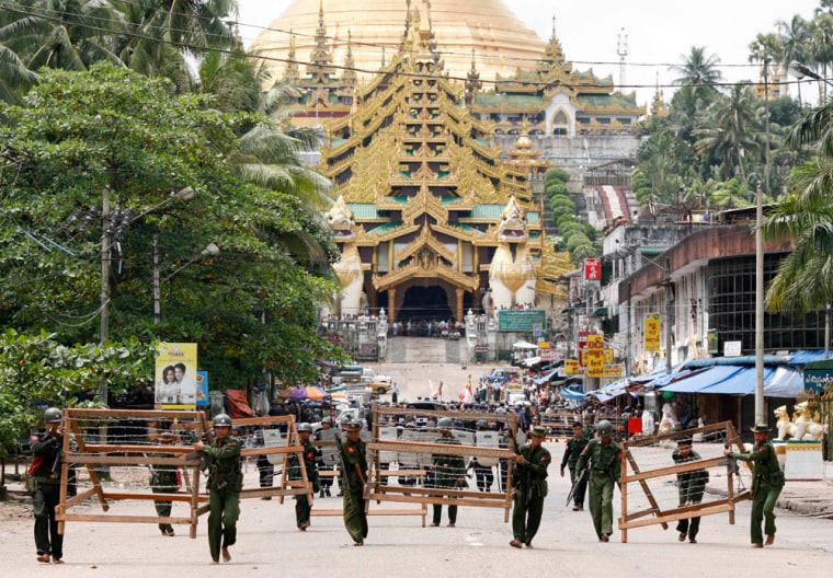 Military officials set up barricades after halting monks from entering the Shwedagon Pagoda in Yangon