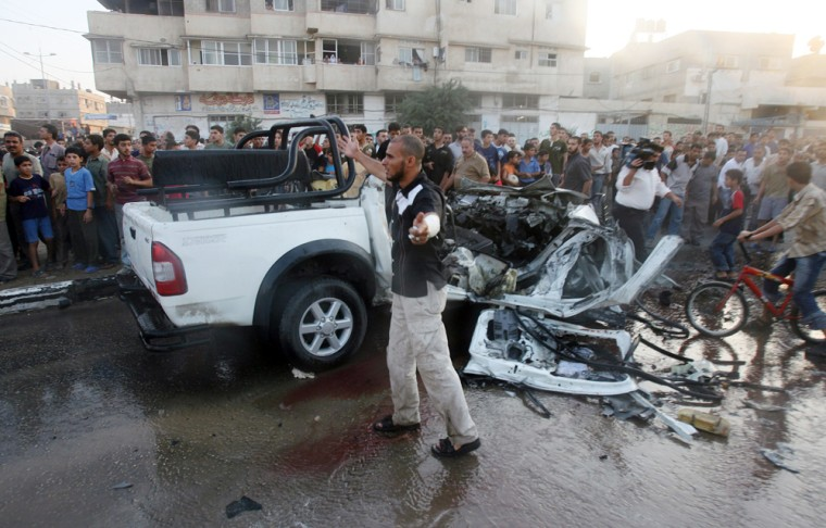 Palestinians gather around the wreckage of a vehicle damaged in an Israeli air raid Wednesday in the heart of Gaza City.