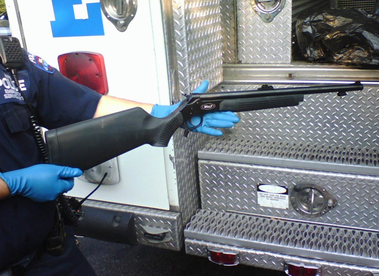 A New York City police officer displays a rifle that was taken from a masked college student who was carrying it around St. John's University in Queens. The school activated its new text-messaging system on Wednesday to alert students to potential danger.