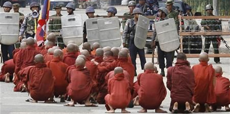 Buddhist monks pray at a roadblock in Yangon, Myanmar, on Thursday. About 10,000 anti-government protesters gathered in downtown Yangon despite a violent crackdown by security forces that drew international appeals for restraint by Myanmar's ruling junta.