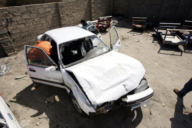 Hussam Hassan inspects his father's car, which was damaged in the shooting incident involving Blackwater USA security guards on Sept. 20, in Mahmoudiya, south of Baghdad.At least 11 Iraqis died in the incident.