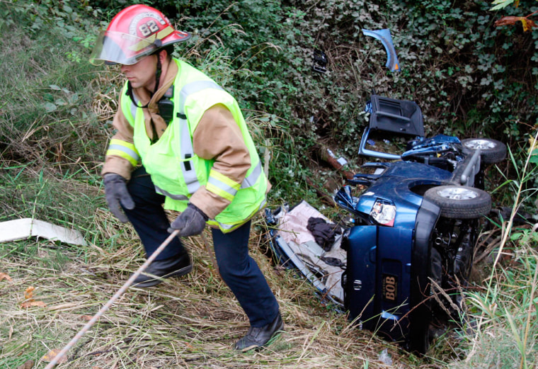 A firefighter on Thursday pulls himself up from a steep ravine where Tanya Rider was found inside her crashed vehicle.
