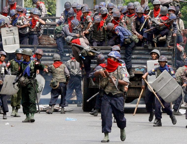 Riot police and military personnel arrive at the scene of an anti-government protest in Yangon's city centre