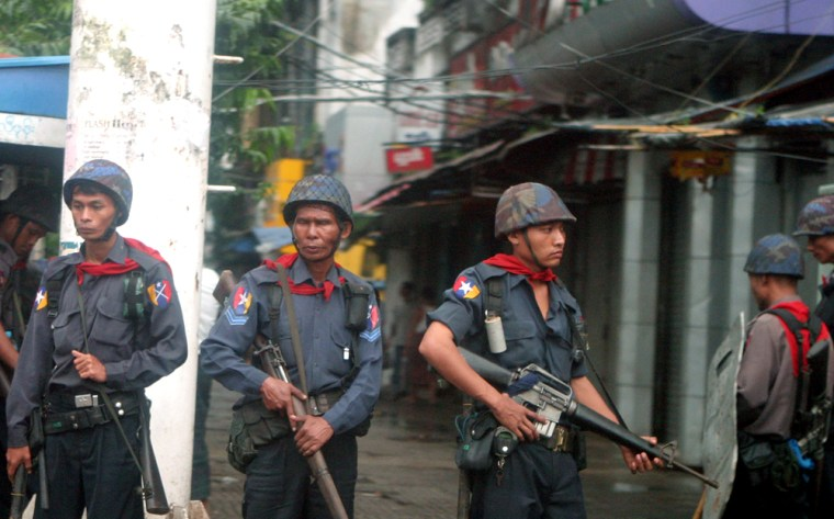 Soldiers take their positions along a street to quell defiant protesters who gathered in pockets to continue protests against the military junta Saturday in Yangon, Myanmar.