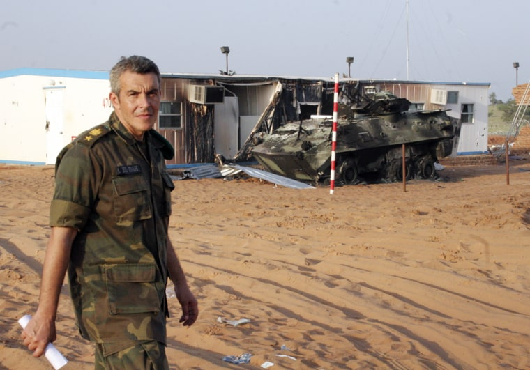 An African Union officer from Egypt inspects the remains of charred barracks and armored personnel carrier Sundayafter the rebel attack.