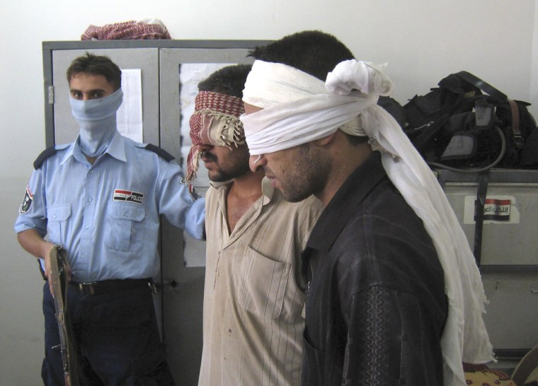 An Iraqi police officer guards two detaineeswhowere arrested astheytried to launch a Katusha rocket at the Kirkuk airport, north of Baghdad, on Sunday.